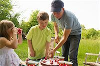Father with two children cutting birthday cake outdoors Stock Photo - Premium Royalty-Freenull, Code: 649-06845260