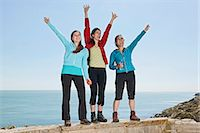 Three female friends waving from wall at coast Stock Photo - Premium Royalty-Freenull, Code: 649-06845284
