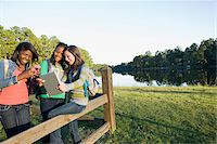 Pre-teen girls sitting on fence, looking at tablet computer and cellphone, outdoors Stock Photo - Premium Royalty-Freenull, Code: 600-06847443