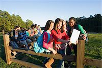 Group of pre-teens sitting on fence, looking at tablet computer and cellphones, outdoors Stock Photo - Premium R
