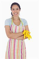 rubber apron woman - Woman smiling while holding rubber gloves and wearing an apron Stock Photo - Royalty-Freenull, Code: 400-06863559
