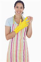 rubber apron woman - Smiling woman in apron taking off rubber gloves Stock Photo - Royalty-Freenull, Code: 400-06863561