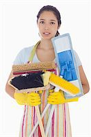 rubber apron woman - Frowning woman in apron and rubber gloves holding brushes and mops Stock Photo - Royalty-Freenull, Code: 400-06863565