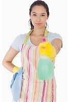 rubber apron woman - Smiling woman spraying cleaner in apron and rubber gloves Stock Photo - Royalty-Freenull, Code: 400-06863614