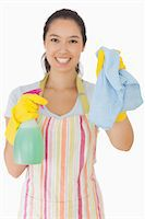 rubber apron woman - Smiling young woman holding up rag and spray bottle in apron and rubber gloves Stock Photo - Royalty-Freenull, Code: 400-06863642