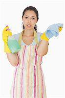 rubber apron woman - Overworked woman holding rag and spray bottle in apron and rubber gloves Stock Photo - Royalty-Freenull, Code: 400-06863644