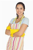 rubber apron woman - Smiling young woman with crossed arms wearing rubber gloves and apron Stock Photo - Royalty-Freenull, Code: 400-06863684