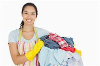 rubber apron woman - Laughing woman holding laundry basket wearing apron and rubber gloves Stock Photo - Royalty-Freenull, Code: 400-06863692