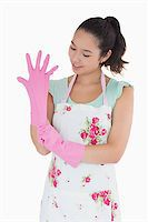 rubber apron woman - Smiling woman pulling on rubber gloves Stock Photo - Royalty-Freenull, Code: 400-06863888