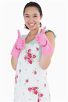 rubber apron woman - Smiling woman wearing rubber gloves giving thumbs up on a white background Stock Photo - Royalty-Freenull, Code: 400-06863889