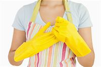 rubber apron woman - Woman taking off her rubber gloves in apron Stock Photo - Royalty-Freenull, Code: 400-06866387