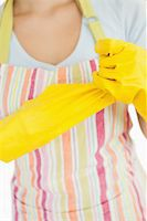 rubber apron woman - Woman pulling off rubber gloves wearing an apron Stock Photo - Royalty-Freenull, Code: 400-06866389