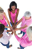 Group of women wearing pink and ribbons for breast cancer putting hands together on white background Stock Photo - Royalty-Freenull, Code: 400-06891616