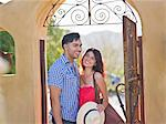 Young couple smiling together at entrance to villa Stock Photo - Premium Royalty-Freenull, Code: 614-06895975