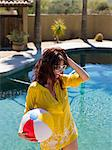 Young woman holding beach ball at poolside, smiling Stock Photo - Premium Royalty-Free, Artist: R. Ian Lloyd, Code: 614-06895993