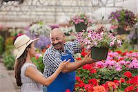 Mature man serving young woman in garden centre, smiling Stock Photo - Premium Royalty-Freenull, Code: 614-06896182