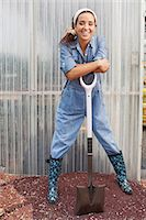 Young woman in dungarees leaning on spade in garden centre, portrait Stock Photo - Premium Royalty-Freenull, Code: 614-06896321
