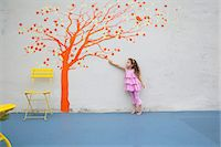 Girl pointing to orange tree mural on wall Stock Photo - Premium Royalty-Freenull, Code: 614-06896702