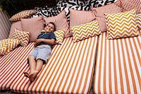 Boy relaxing on striped outdoor  furniture with cushions Stock Photo - Premium Royalty-Freenull, Code: 614-06896711