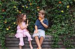 Brother and sister eating ice lollies by plants Stock Photo - Premium Royalty-Free, Artist: Cultura RM, Code: 614-06896713