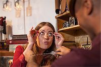 funny looking people - Woman in vintage shop trying on glasses and pulling faces Stock Photo - Premium Royalty-Freenull, Code: 614-06896725