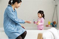 Mother with female toddler standing in bath with tooth brush Stock Photo - Premium Royalty-Freenull, Code: 614-06896921