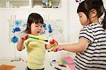 Two young sisters holding paint bottle and brushes