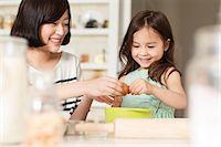 Mother and young daughter cracking egg into mixing bowl Stock Photo - Premium Royalty-Freenull, Code: 614-06896959