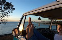 Young woman with feet up on camper van window Stock Photo - Premium Royalty-Freenull, Code: 614-06897280