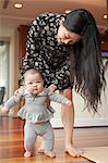 Mother helping baby girl to walk Stock Photo - Premium Royalty-Freenull, Code: 614-06897325