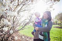 Portrait of baby girl and grandmother next to magnolia blossom Stock Photo - Premium Royalty-Freenull, Code: 614-06897399