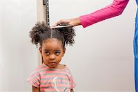 Nurse measuring height of young patient Stock Photo - Premium Royalty-Freenull, Code: 614-06897475
