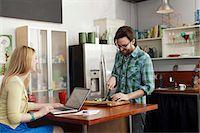 Woman on laptop computer, man chopping vegetables Stock Photo - Premium Royalty-Freenull, Code: 614-06897561