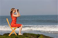 Mature woman sitting on chair on beach with binoculars Stock Photo - Premium Royalty-Freenull, Code: 614-06897787