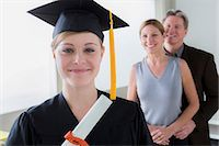 Teenage girl wearing mortarboard with parents in background Stock Photo - Premium Royalty-Freenull, Code: 614-06897832