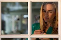 Portrait of young woman looking through window Stock Photo - Premium Royalty-Freenull, Code: 614-06897928