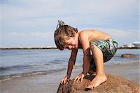 Boy crouching on rock on beach Stock Photo - Premium Royalty-Freenull, Code: 614-06898004