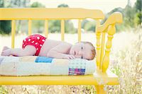 Newborn baby girl lying on yellow bench in field Stock Photo - Premium Royalty-Freenull, Code: 614-06898011