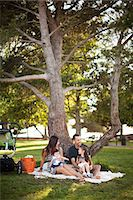 sitting under tree - Family with two children sitting on picnic blanket under tree Stock Photo - Premium Royalty-Freenull, Code: 614-06898058