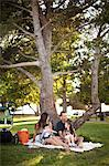 Family with two children sitting on picnic blanket under tree