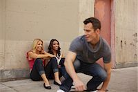 roller skate - Man skating past women sitting on ground Stock Photo - Premium Royalty-Freenull, Code: 614-06898313