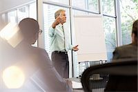 Businessman gesturing at flipchart in meeting Stock Photo - Premium Royalty-Freenull, Code: 6113-06899000