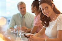 Portrait of smiling businesswoman with cell phone in meeting Stock Photo - Premium Royalty-Freenull, Code: 6113-06899073