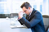person overwhelmed stresss - Businessman with head in hands in conference room Stock Photo - Premium Royalty-Freenull, Code: 6113-06899170