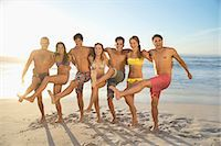 Portrait of smiling friends hugging and kicking on beach Stock Photo - Premium Royalty-Freenull, Code: 6113-06899282