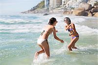 Playful friends in bikinis splashing in ocean Stock Photo - Premium Royalty-Freenull, Code: 6113-06899301