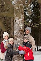 Portrait of happy family hugging tree trunk in snowy woods Stock Photo - Premium Royalty-Freenull, Code: 6113-06899488
