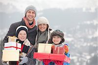 Portrait of happy family with Christmas gifts in snow Stock Photo - Premium Royalty-Freenull, Code: 6113-06899489