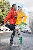 people with umbrellas in the rain - Happy couple in wellingtons splashing in rainy street Stock Photo - Premium Royalty-Freenull, Code: 6113-06899525