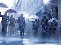people with umbrellas in the rain - Business people with umbrellas running in rain Stock Photo - Premium Royalty-Freenull, Code: 6113-06899526